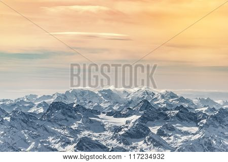 flight over snow mountains with warm cloudy sky in austria