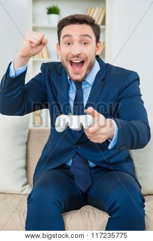 Beautiful young man in suit playing video games