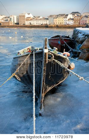 boats covered by frost and ice on Corrib river in Claddagh Galway poster
