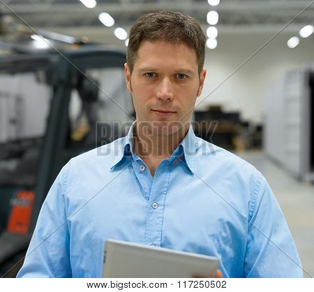 Handsome supervisor with tablet pc at warehouse. poster