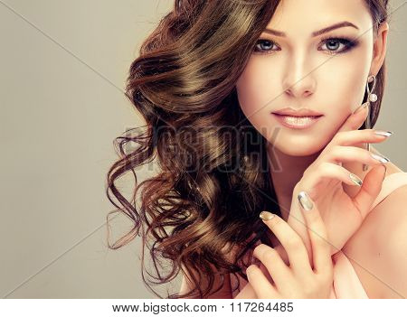 Beautiful girl with long wavy hair . Brunette with curly hairstyle .
