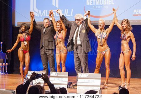 Female Fitness Models Celebrate Their Victory On Stage With Officials