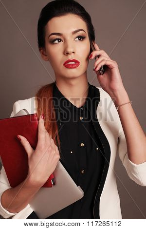 beautiful businesslike woman with dark hair and bright makeup, wears elegant suit