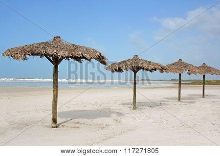 Row Of Grass Beach Cabanas By The Ocean