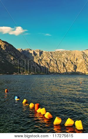 Line of colorful buoys, made of jerrican, mountains in the background