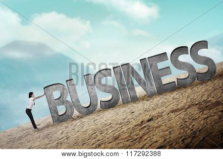 Business Person Pushing 3D Business Word Uphill