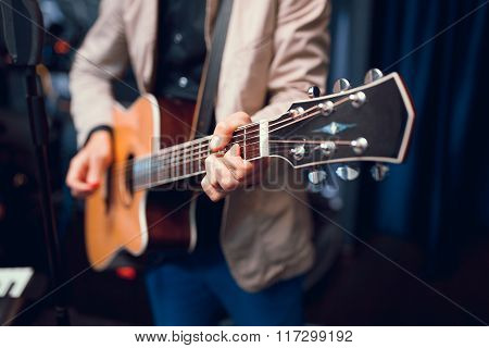 hands playing acoustic guitar