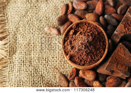 Bowl with aromatic cocoa powder and green leaf on a sacking, close up