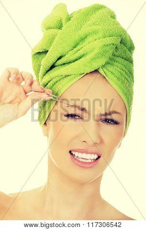 Beautiful woman plucking her eyebrow. poster