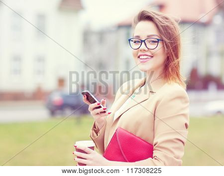 Attractive happy young business woman wearing glasses holding a smartphone, bag and take away coffee standing outdoor in the street