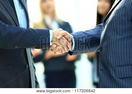 Business handshake. Business man giving a handshake to close the deal poster