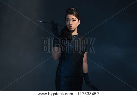 Posh Asian Woman In Retro 1940 Dress Smokes Cigaret.