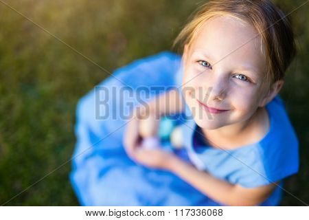 Above view of adorable little girl playing with colorful Easter eggs outdoors on a grass at spring