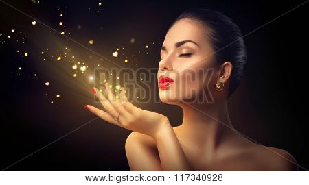 Beauty Young Woman Blowing Magic Dust with golden hearts and stars from her hands. Valentine's Day Holiday Concept. Isolated on black background Beautiful Romantic Girl. Miracle, magic of love