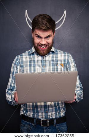 Funny bearded young man using laptop and standing over blackboard background with drawn horns