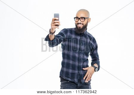 Cheerful baldheaded young african american man with beard in glasses smiling and taking selfie