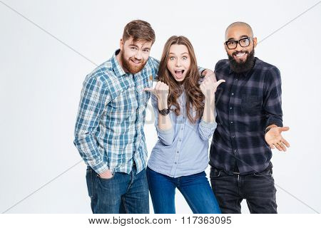 Beautiful amazed young woman standing and pointing on her two bearded handsome friends