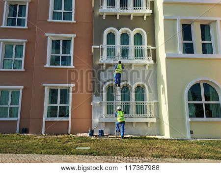 Old building is being re-painted and repaired by workers.