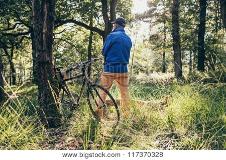 Man Standing In Forest Looking Faraway. Bicycle Standing Against Tree. Rear View.
