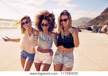 Portrait of three young female friends walking on the sea shore looking at camera laughing. Multiracial young women strolling along a beach. poster
