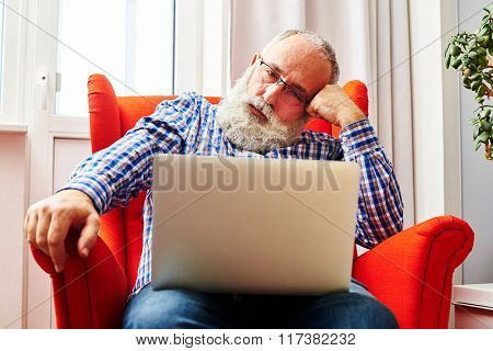 fatigued senior man sitting on the red chair and looking at laptop
