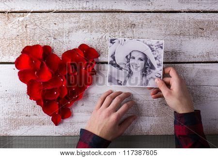 Mans hands holding his girlfriends photo. Red rose petal heart.