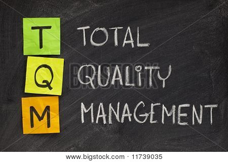 TQM acronym (total quality management) - white chalk handwriting and sticky notes on blackboard poster