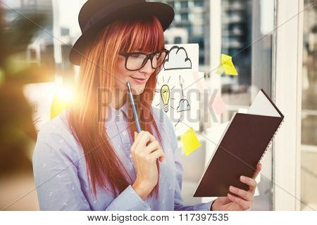 Smiling hipster woman writing notes against adhesive notes on window