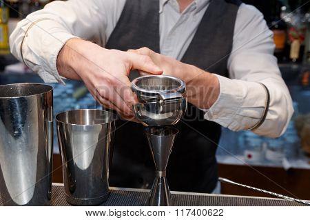 Bartender is squeezing citrus juice in jigger