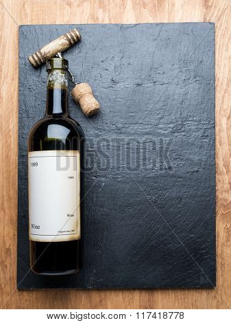 Wine bottle and corkscrew on the graphite board.