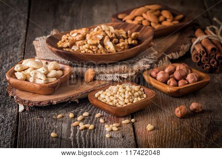 Almonds, Walnuts, Hazelnuts Cashews And Pine Nuts In Wooden Bowls