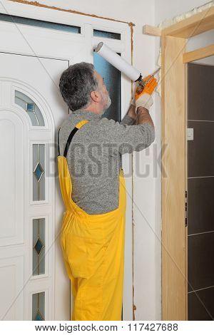 Worker Installing Wooden Door, Using Polyurethane Foam