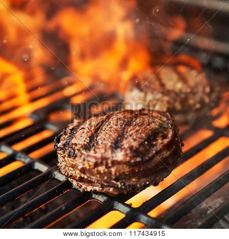grilling filet mignon steaks on grill with flames shot with extreme selective focus