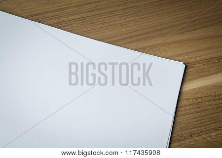 Blank sheets of white paper on wooden desk ready for artwork.