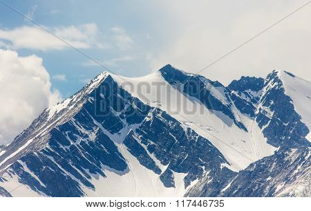 Snow-capped mountain peaks under the clouds , blue, reflectio
