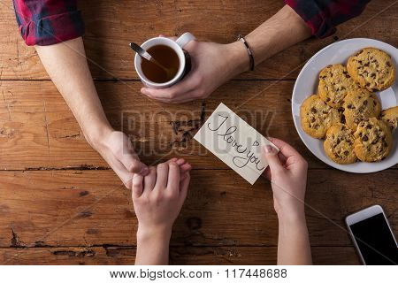 Unrecognizable man and woman hands. I love you note. Tea and cookies. Valentines day composition. Studio shot on brown wooden background. poster