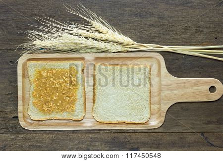 selective focus of bread and peanut butter on wood background with wheat poster