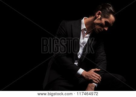 businessman in black with open shirt pose in dark studio background while looking down touching hands