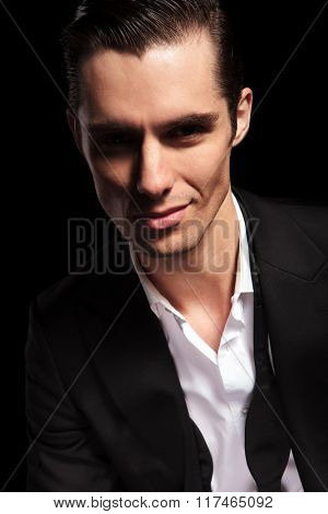 portrait of handsome businessman with open shirt smiling in dark studio background
