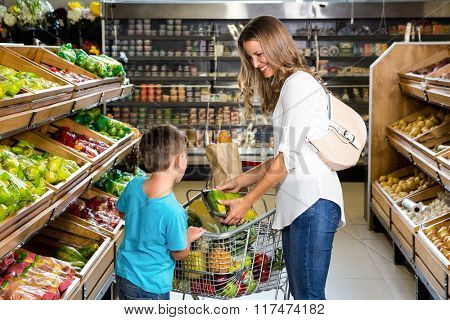 Mother and son doing shopping in grocery store