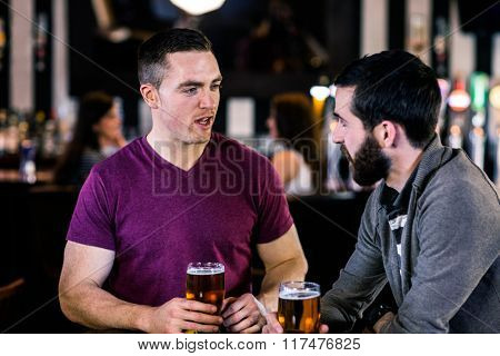 Friends talking and having a pint in a bar