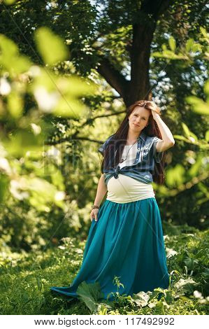 Young Pregnant Woman In The Summer Park