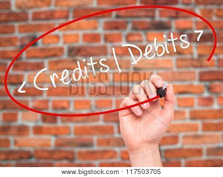 Man Hand Writing Credits - Debits With Black Marker On Visual Screen.