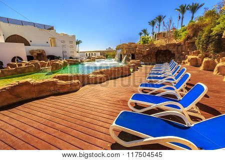 Swimming pool with artificial waterfall and sun loungers