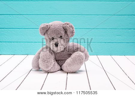 Teddy bear sitting on white wooden floor with blue-green background lonely
