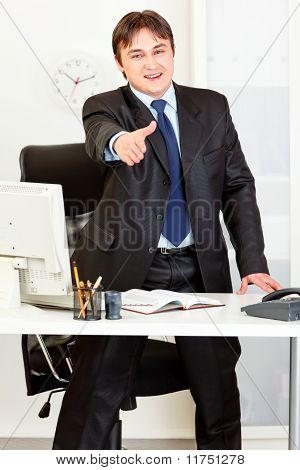 Smiling modern businessman standing at office desk and stretches out hand for handshake