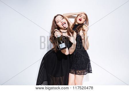 Two young women in night dress drinking champagne and showing tongue isolated on a white background