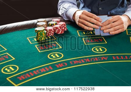 Closeup of poker player with playing cards and chips
