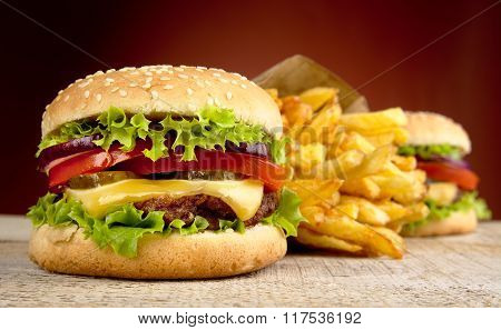 Cheeseburger And French Fries On Red Spotlight On Wooden Table