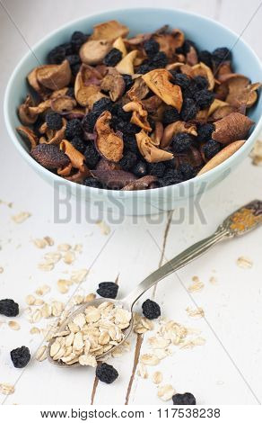 Blue Plate With Dried Apples And Berries And Oatmeal On A White Wooden Background. Healthy Food.